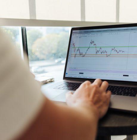man looking at stocks on laptop
